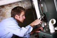HVAC tech repairing a furnace in a metro Birmingham, AL home